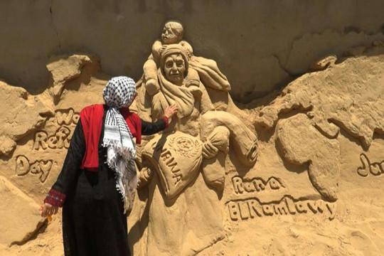 النحاتة رنا الرملاوي تُجسد في الرمال قضية اللاجئين